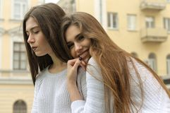Two girls rest and inflate bubbles of chewing gum. They both have long brown hair that is long to the waist and they are dressed in identical white sweaters Royalty Free Stock Photography