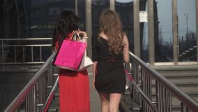 Two girls rest after a successful shopping. Friends spend time together in the city. SLOW MOTION. Beautiful young girls go near the shop windows. The best stock video