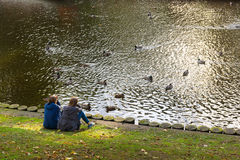 Two girls resting on the bank of a pond with ducks Royalty Free Stock Photos