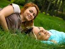 Two girls resting on the grass Royalty Free Stock Photos