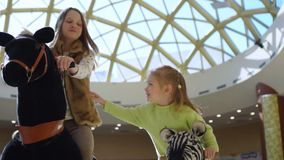 Two girls ride an attraction in shopping center. On this video you see as the little girl rides a toy horse during stay in big shopping center. The little girl stock video footage