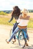 Two girls ride bicycles on road Royalty Free Stock Image