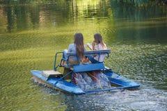 Two girls ride on catamaran on the lake Royalty Free Stock Image
