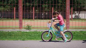 Two girls ride outdoor bicycles. Girls ride bicycles, meet and leave in different directions on bicycles stock video