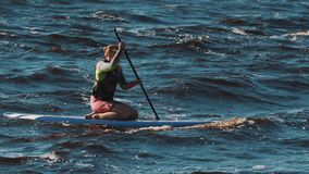Two girls rides surfing boards while sitting on her knees and rows with paddle. Two girls competing and rides surfing boards while sitting on her knees and rows stock footage