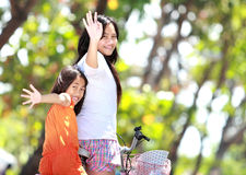Two girls riding bicycle. Portrait of smiling litte girls riding bicycle together in green nature Royalty Free Stock Images