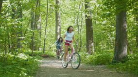 Two girls riding bicycles on the path in the Park. Telephoto shot stock video footage