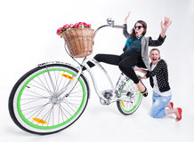 Two girls riding a bike making funny faces -  on bluish background Royalty Free Stock Images