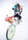 Two girls riding a bike making funny faces -  on bluish background Stock Photos