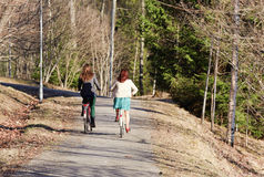 Two girls riding a bike in the park Stock Photo