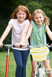 Two Girls Riding Bike And Scooter Together. Girls Playing On Bike And Scooter Outdoors Royalty Free Stock Images