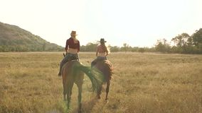 Two girls riding a horse in a field at sunset. Two young girls with long hair and a cowboy hat galloping on horseback in the field at sunset, slow motion. Two stock video