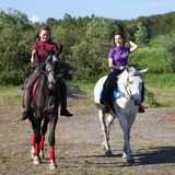 Two girls riding horses Royalty Free Stock Photo