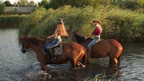 Two girls bathe their horses in the lake, slow mo. Two girls riding on horses bathe the horses in the lake on a background of reeds stock footage