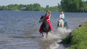 Two girls are riding horses on a beach. Horses race on water. Beautiful sunset is seen in this shot. Two girls are riding horses on a beach. Horses race on stock video footage