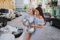 Two girls are riding on one motorcycle. Chinese girl is in a front. Brunette girl is sitting in the middle. The last one Royalty Free Stock Photos