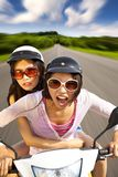 Two girls riding scooter. On the road Royalty Free Stock Photo