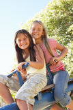 Two Girls Riding On See Saw In Playground. Smiling At Camera Royalty Free Stock Photos