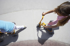 Two girls (4-6) riding toy push scooters in playground, side view, overhead view Royalty Free Stock Photo
