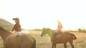 Two girls riding a troubled horse in summer field. stock video