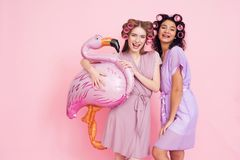 Two girls with hair curlers and pink flamingo baloon. They are celebrating women`s day March 8. Royalty Free Stock Photos