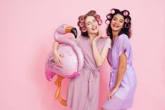 Two girls with hair curlers and pink flamingo baloon. They are celebrating women`s day March 8. Royalty Free Stock Photography