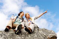 Two girls on a rock. Two women take a break from trekking and rest on a rock outdoors royalty free stock photos