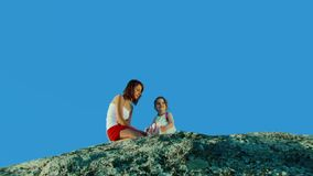 Two girls on a rock against the blue sky stock video