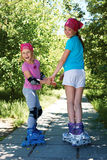 Two girls in roller skates looking at the camera. Royalty Free Stock Images