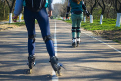Two girls on roller skates ride along the road next to each other Royalty Free Stock Images