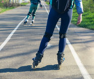 Two girls on roller skates ride along the road next to each other Stock Photography