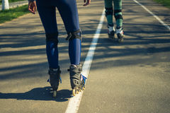 Two girls on roller skates ride along the road next to each other Stock Image