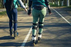 Two girls on roller skates ride along the road next to each other Stock Photo