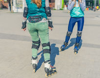 Two girls rollers meet each other in the park Royalty Free Stock Photography