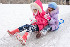 Two girls rolling ice slides Royalty Free Stock Photo