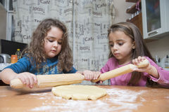 Two girls rolling out dough on kitchen table Royalty Free Stock Photography