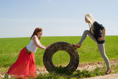 Two girls rolls wheel Royalty Free Stock Photo