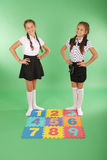 Two girls on rug with numbers Stock Images