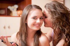 Two girls rumoring Stock Images
