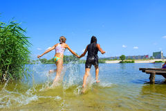 Two girls run into water Stock Photo