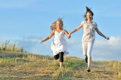 Two girls running across the field Royalty Free Stock Image