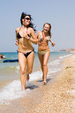 Two girls running along the seashore Royalty Free Stock Photo