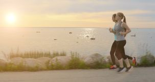 Two girls running along walkway at the seaside in the evening at sunset in the summer. In the background beautiful scenic sunset in the sea stock video footage