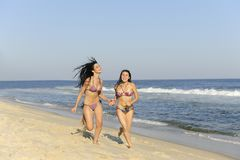 Two girls running on the beach Stock Images