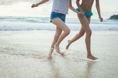 Two girls running on the beach Stock Photos