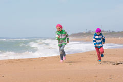 Two girls running on beach seaside Stock Image