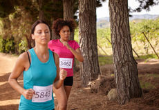 Two girls running a country race Stock Images