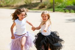 Two girls running with fantacy dresses in park. Royalty Free Stock Photo