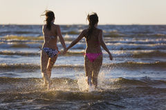 Two girls running in the sea Royalty Free Stock Images