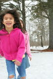 Two girls running through the snow Stock Image